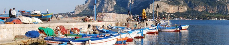 small colorful fisher boats docked in Mondello with Monte Pellegrino in the background, azure sky deep blue sea